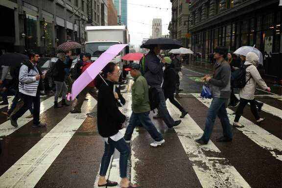 Pedestrians with umbrellas out cross Market Street at Fifth Street in San Francisco.