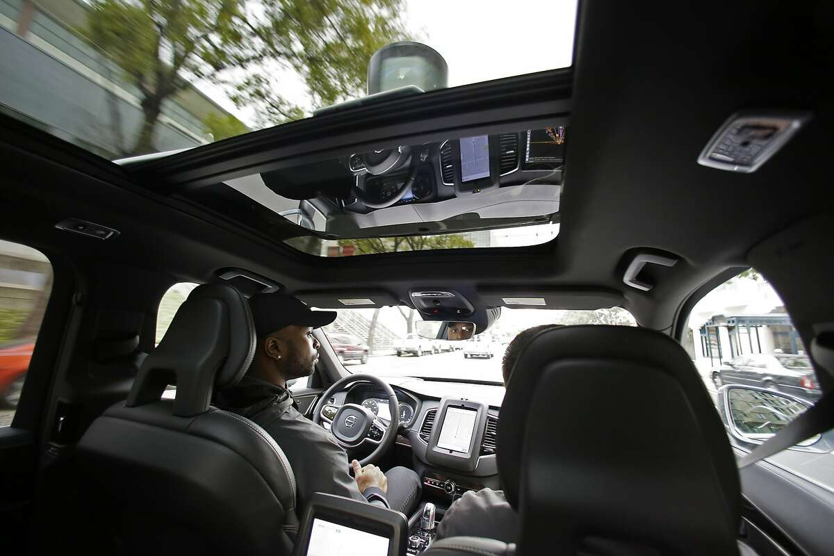 In this photo taken Tuesday, Dec. 13, 2016, Devin Greene sits in the front seat of an Uber driverless car during a test drive in San Francisco. Uber is riding its self-driving cars into a legal showdown with California regulators. The ride-hailing company is refusing to obey demands by the state's Department of Motor Vehicles that it stop picking up San Francisco passengers in specially equipped Volvo SUVs. Hours after Uber launched the self-driving service Wednesday, Dec. 14, the DMV warned it was illegal because the cars did not have a special permit. (AP Photo/Eric Risberg)