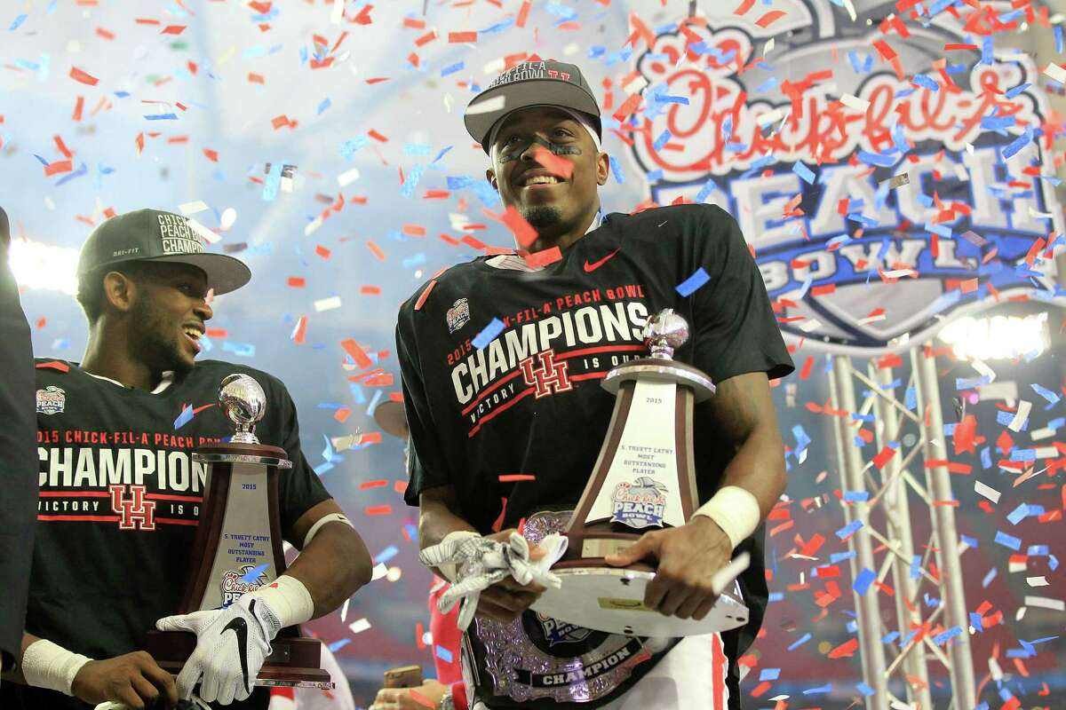 Houston Cougars quarterback Greg Ward Jr. (1) and Houston Cougars cornerback William Jackson III (3) hold their player of the game trophies as the Houston Cougars celebrate their 38-24 win over Florida State University in the Chick-fil-A Peach Bowl at the Georgia Dome on Thursday, Dec. 31, 2015, in Atlanta. ( Elizabeth Conley / Houston Chronicle )