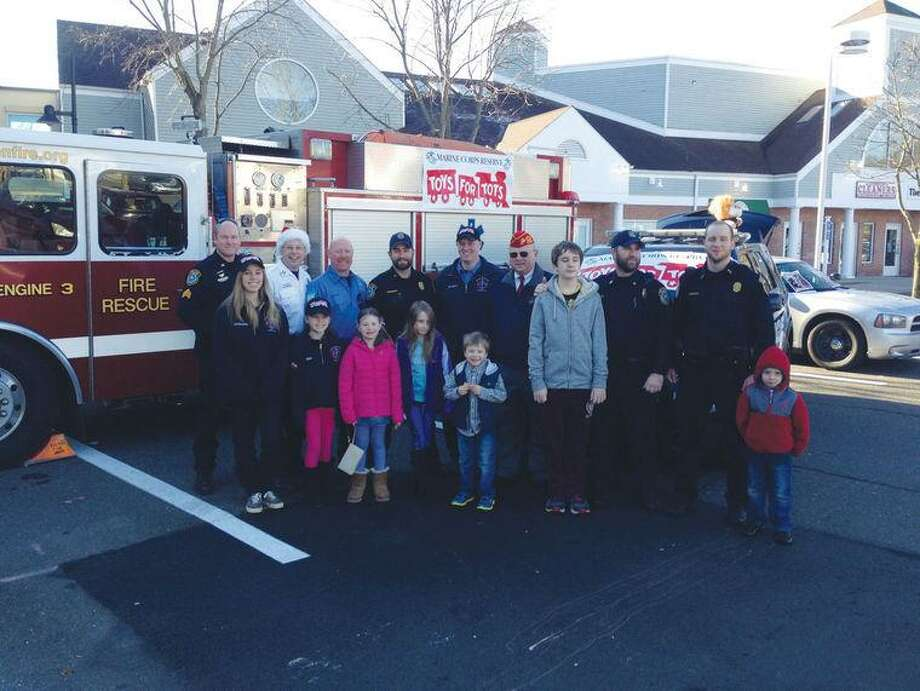 Police officers, Toys for Tots organizers and children from the community pose in front of a fire engine stuffed with gifts. Photo: Contributed Photo