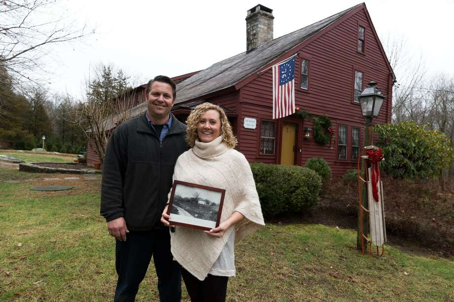 Chris and Elaina Weiser stand in front of their home holding an old photo of what the Satlbox style house used to look like on 6 Great Ring Road Monroe, Conn. on Wednesday, December 7, 2016. Photo: Chris Palermo / For Hearst Connecticut Media / Connecticut Post Freelance