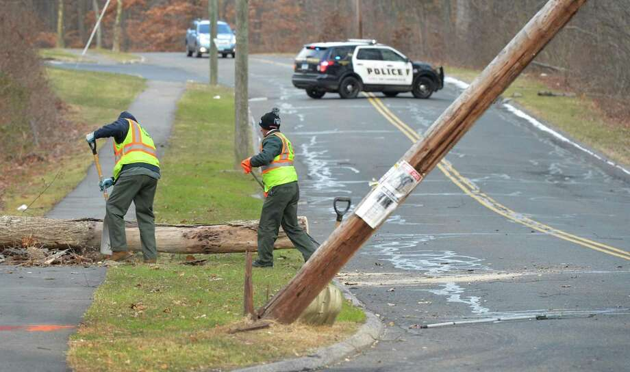 A utility pole that was hit and snapped by a falling tree brought down by high winds, closes Knowalot Lane at Cranbury school as Norwalk Public Works begins clean up on Thursday December 15, 2016 in Norwalk Conn. Photo: Alex Von Kleydorff / Hearst Connecticut Media / Connecticut Post