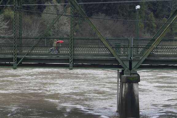 Residents walk across the old Guerneville Bridge as the Russian River exceeds flood stage in Guerneville, Calif. on Friday, Dec. 12, 2014.