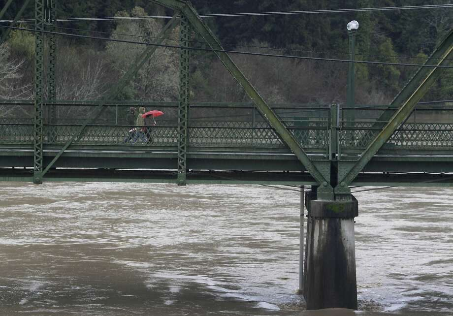 """Residents walk across the old Guerneville Bridge as the Russian River exceeds flood stage in Guerneville, Calif. on Friday, Dec. 12, 2014. On Thursday, rain is expected to raise the river water level at Guerneville to 28.9 feet — one inch below the """"action stage"""" that calls for increased monitoring and extra caution. Photo: Paul Chinn, The Chronicle"""