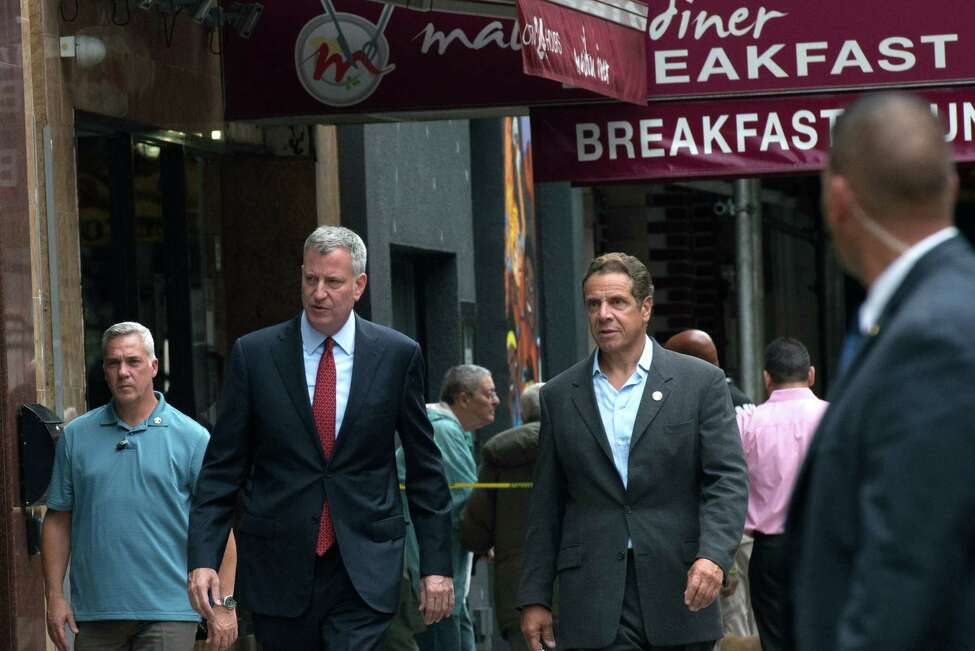 NEW YORK, NY - SEPTEMBER 18: New York City Mayor Bill de Blasio (L) and New York Gov. Andrew Cuomo tour the site of the bomb blast on 23rd St. in Manhattan's Chelsea neighborhood on September 18, 2016 in New York City. An explosion that injured 29 people which went off in a construction dumpster is being labeled an