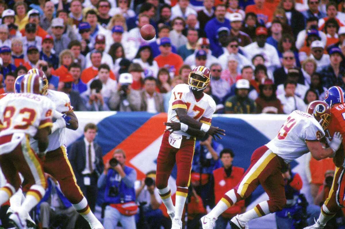 Doug Williams shook off an early knee injury to throw for four touchdowns in the second quarter to lead Washington over Denver and become the first African-American quarterback to win a Super Bowl.