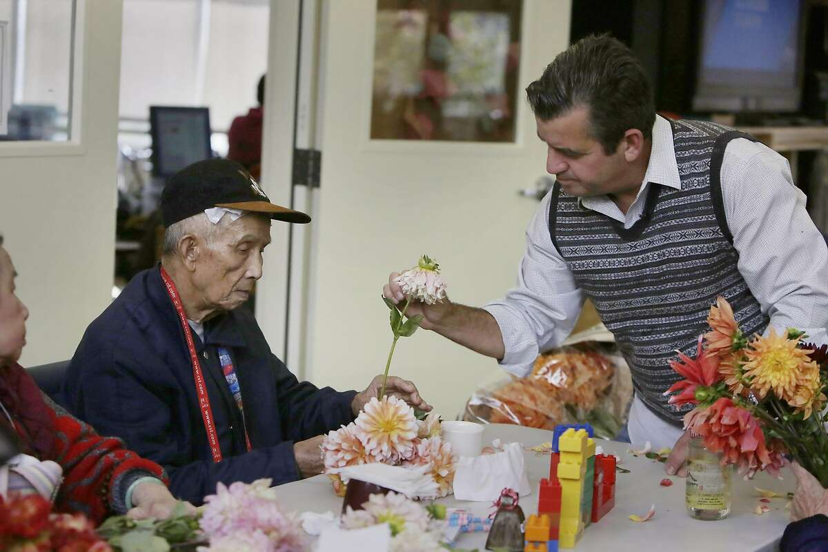 Darren Fanelli (right), aactivity director SteppingStone Mission Creek Day Health, shows client Pek Toy Chew (left) a flower, which are regularly donated by Piazza Wholesale owner Joel Phmah, which provides an activity for seniors at SteppingStone on Friday, October 7, 2016 in San Francisco, California.