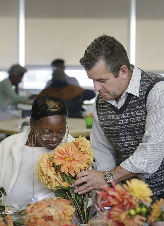 Darren Fanelli (right), activity director SteppingStone Mission Creek Day Health, holds a bouquet of flowers for Rachel Lewis (left) to smell before handing them to her during an activity for seniors at SteppingStone on Friday, October 7,  2016 in San Francisco, California. Photo: Lea Suzuki, The Chronicle