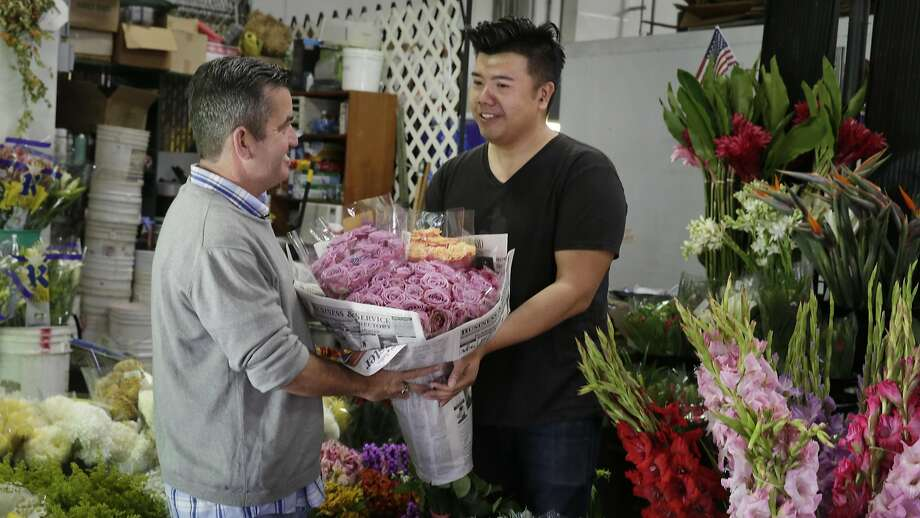 Joel Phmah, owner Piazza Wholesale, hands Darren Fanelli bouquets of flowers he donates to be used in an activity for the seniors at SteppingStone. Photo: Lea Suzuki, The Chronicle