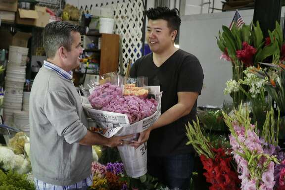Joel Phmah, owner Piazza Wholesale, hands Darren Fanelli,activity director SteppingStone Mission Creek Day Health,, bouquets of flowers he donates to be used in an activity for the seniors at SteppingStone on Friday, October 21,  2016 in San Francisco, California.