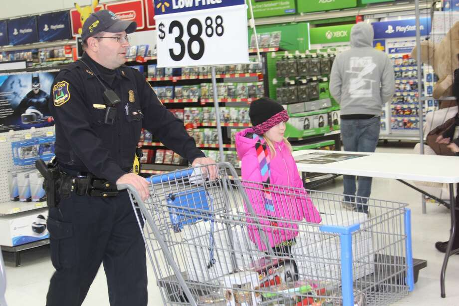 Local fire, EMS, police and other authorities roamed through Wal-Mart Wednesday afternoon with children from local elementary schools as part of Shop with a Hero. Photo: Bradley Massman/Huron Daily Tribune
