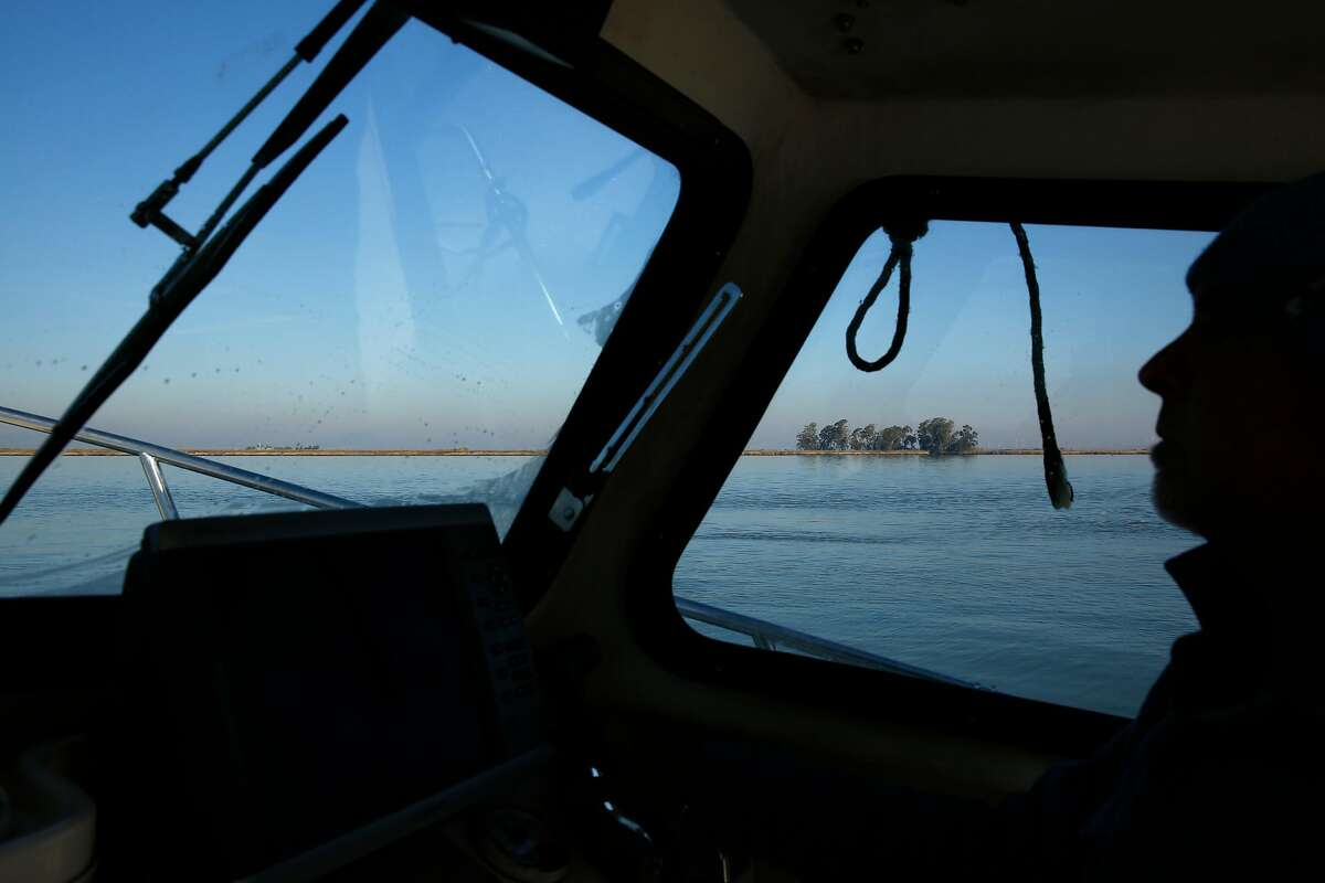 John Sweeney drives a boat in 2015 near Pittsburg. A state appeals court has reinstated a cleanup order against him after he deposited large amounts of landfill into Suisun Bay marsh waters to clear the way for a duck club and kite-surfing center.