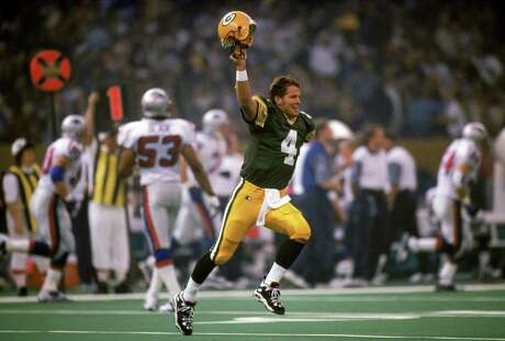 NEW ORLEANS - JANUARY 26:  Quarterback Brett Favre #4 of the Green Bay Packers celebrates his first quarter touchdown pass to wide receiver Andre Rison #26 in Super Bowl XXXI against the New England Patriots at the Louisiana Superdome on January 26, 1997 in New Orleans, Louisiana. The Packers won 35-21.  (Photo by Andy Hayt/Getty Images)