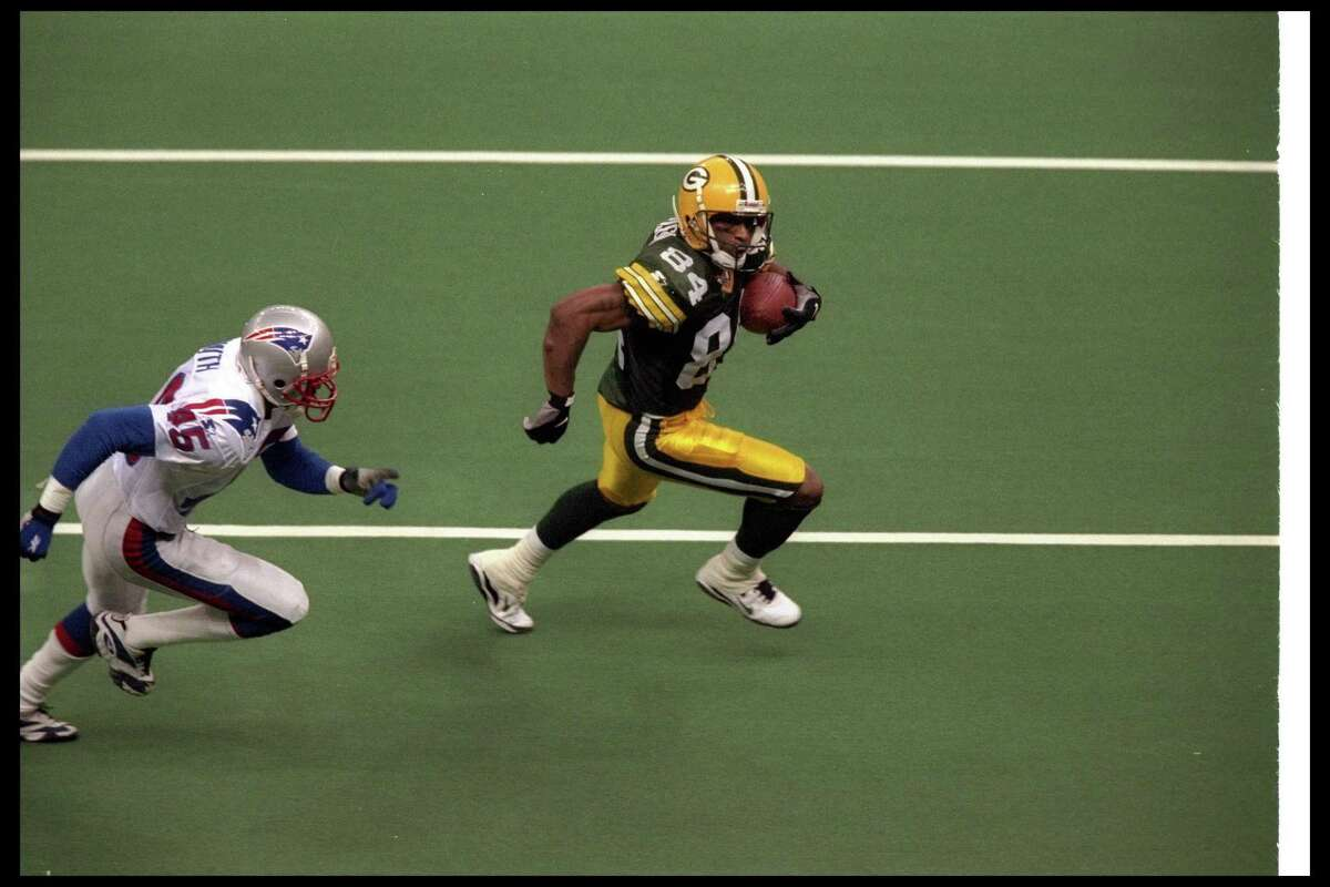 26 Jan 1997: Wide receiver Andre Rison of the Green Bay Packers (right) moves the ball as New England Patriots defensive back Otis Smith chases him during Super Bowl XXXI at the Superdome in New Orleans, Louisiana. The Packers won the game, 35-21. Manda