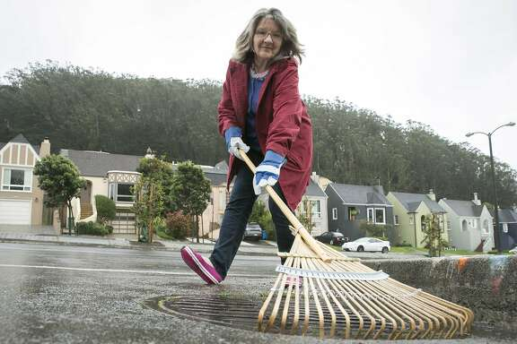 Beth Silver clears debris from a drain on Thursday, Dec. 15, 2016 in San Francisco, Calif. Silver keeps watch of two drains near her home as part of the Adopt-a-Drain program. Approximately 500 of the city's 750 drains have been adopted. This particular drain Silver named Duane.