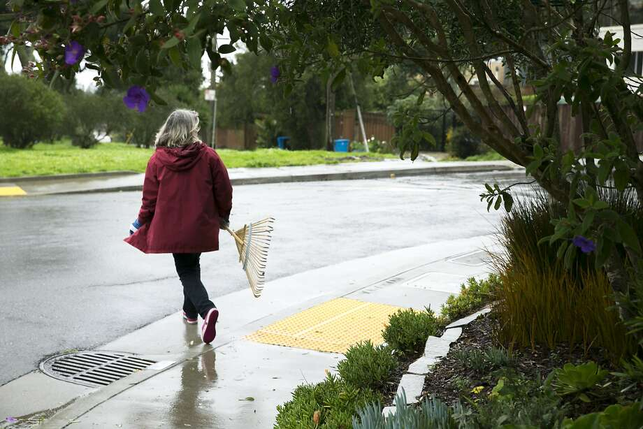 Beth Silver walks past one storm drain to clean another. More than 900 of the city's 25,000 drains have been adopted. Photo: Santiago Mejia, The Chronicle