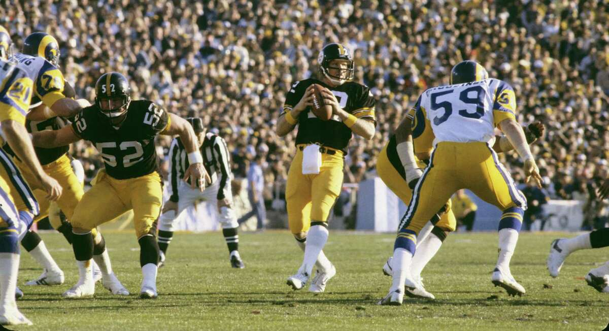 Pittsburgh Steelers quarterback Terry Bradshaw (12) takes the snap from center Mike Webster (52), both members of the Pro Football Hall of Fame, during Super Bowl XIV, a 31-19 victory over the Los Angeles Rams on January 20, 1980, at the Rose Bowl in Pasadena, California. (Photo by Nate Fine/Getty Images)