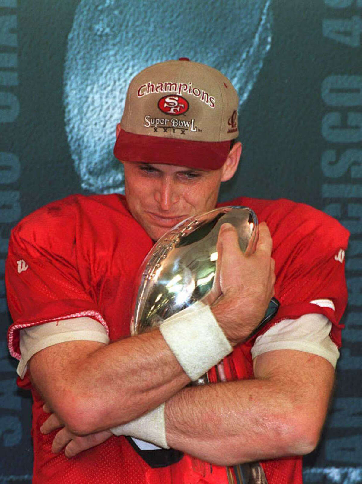 MIAMI, FL - JANUARY 29: San Francisco 49ers quarterback Steve Young hugs the Vince Lombardi trophy 29 January 1995 after being named the Most Valuable Player of Super Bowl XXIX. Young threw a record six touchdown passes as the 49ers defeated the San Diego Chargers 49-26 and became the first team to win five Super Bowls. (COLOR KEY: Jersey is red.) AFP PHOTO (Photo credit should read Roberto SCHIMDT/AFP/Getty Images)