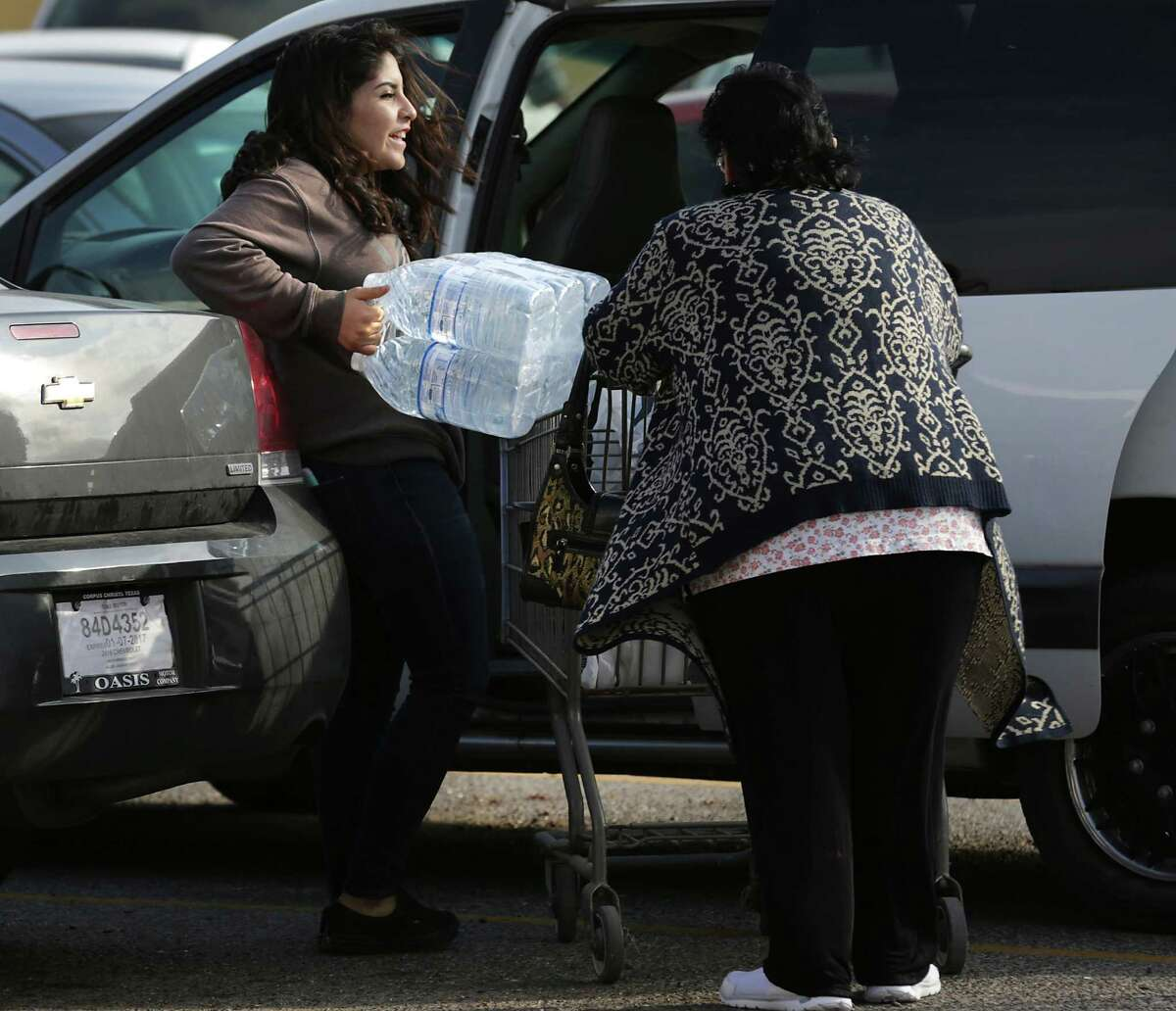Lia Ramos, left, struggles with her family's limit of water purchased at an HEB as Corpus Christi deals with it's public water system being contaminated. Her great grandmother Almo Ramos is at right.