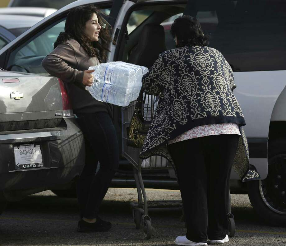 Lia Ramos, left, struggles with her family's limit of water purchased at an HEB as Corpus Christi deals with it's public water system being contaminated. Her great grandmother Almo Ramos is at right. Photo: Bob Owen, Staff / San Antonio Express-News / ©2016 San Antonio Express-News