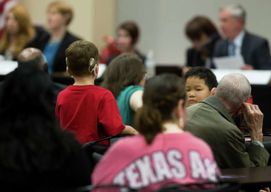A child listens to representatives from the U.S. Department of Education's Office of Special Education and Rehabilitative Services (OSERS) and the Texas Education Agency (TEA) as they make initial remarks, Monday, Dec. 12, 2016, in Houston. The hearing will provide parents and school officials the opportunity to comment on the timely identification and evaluation of students with disabilities. ( Marie D. De Jesus / Houston Chronicle ) Photo: Marie D. De Jesus, Staff / © 2016 Houston Chronicle