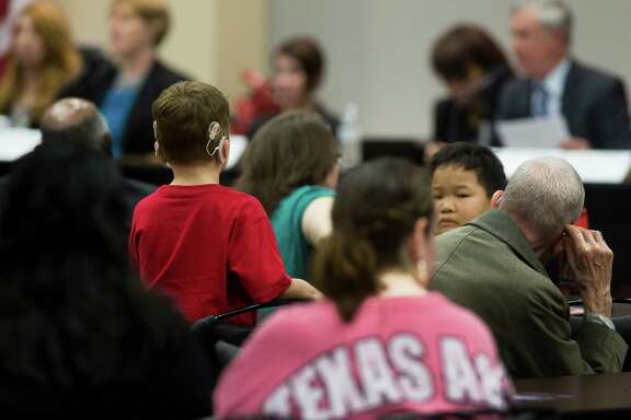 A child listens to representatives from the U.S. Department of Education's Office of Special Education and Rehabilitative Services (OSERS) and the Texas Education Agency (TEA) as they make initial remarks, Monday, Dec. 12, 2016, in Houston. The hearing will provide parents and school officials the opportunity to comment on the timely identification and evaluation of students with disabilities. ( Marie D. De Jesus / Houston Chronicle )