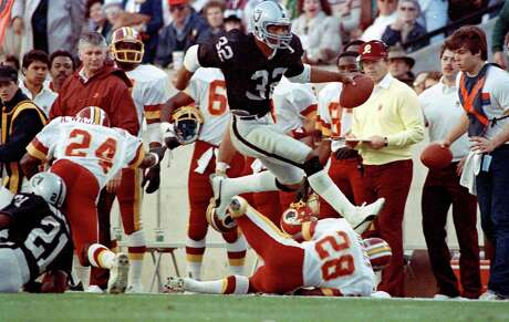 FILE - In this Jan. 22, 1984, file photo, Los Angeles Raiders running back Marcus Allen high-steps his way down the sideline past Washington Redskins' Anthony Washington (24) and Todd Bowles (28) during NFL football's XVIII in Tampa, Fla. Allen rushed for a Super Bowl-record 191 yards on 20 carries and scored two touchdowns as the Raiders trounced the Redskins, 38-9. (AP Photo/File)