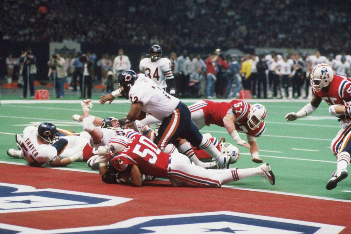 """NEW ORLEANS, LA - JANUARY 26, 1986: Defensivelineman William """"The Refrigerator"""" Perry #72, of the Chicago Bears, leans forward to score a 1-yard touchdown during Super Bowl XX on January 26, 1986 at the Superdome in New Orleans, Louisiana. The Bears beat the Patriots, 46-10. William Perry8611 (Photo by: Kidwiler Collection/Diamond Images/Getty Images)"""
