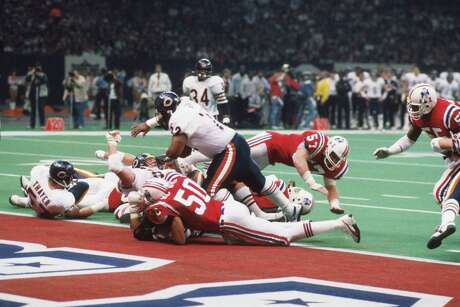 "NEW ORLEANS, LA - JANUARY 26, 1986:  Defensivelineman William ""The Refrigerator"" Perry #72, of the Chicago Bears, leans forward to score a 1-yard touchdown during Super Bowl XX on January 26, 1986 at the Superdome in New Orleans, Louisiana.  The Bears beat the Patriots, 46-10. William Perry8611 (Photo by:  Kidwiler Collection/Diamond Images/Getty Images)"