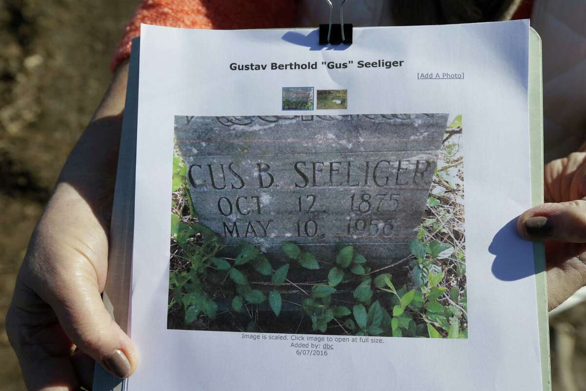 Barbara Davidson holds a copy of a photo of the headstone of family member Gus Seeliger. It is among several missing from Aldine Cemetery after a work crew using heavy equipment cleared the site.