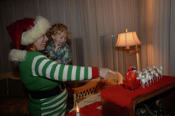 Rachel Shajari and son Aidan, 2, enjoy taking in the holiday decor at Thursday night's A Vintage Christmas at the Chambers House. Visitors got a glimpse into Christmas past as vintage ornaments, cards, and toys decorated the historic home, reflecting on the family's holiday celebrations from the 1920's through the '40's. Refreshments were served and musical entertainment was provided by the Sweet Adelines, who kept the festivities alive with their a cappella renditions of Christmas carol classics.  Photo taken Thursday, December 15, 2016 Kim Brent/The Enterprise