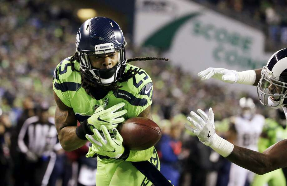 Seattle Seahawks cornerback Richard Sherman, left, bobbles a pass intended for Los Angeles Rams wide receiver Kenny Britt, right, in the first half of an NFL football game, Thursday, Dec. 15, 2016, in Seattle. (AP Photo/Elaine Thompson) Photo: Elaine Thompson/AP