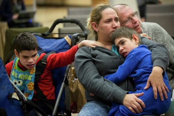Yajaira Hernandez comforts her sons Edwin, left, and Harry while she listens at the Austin session.