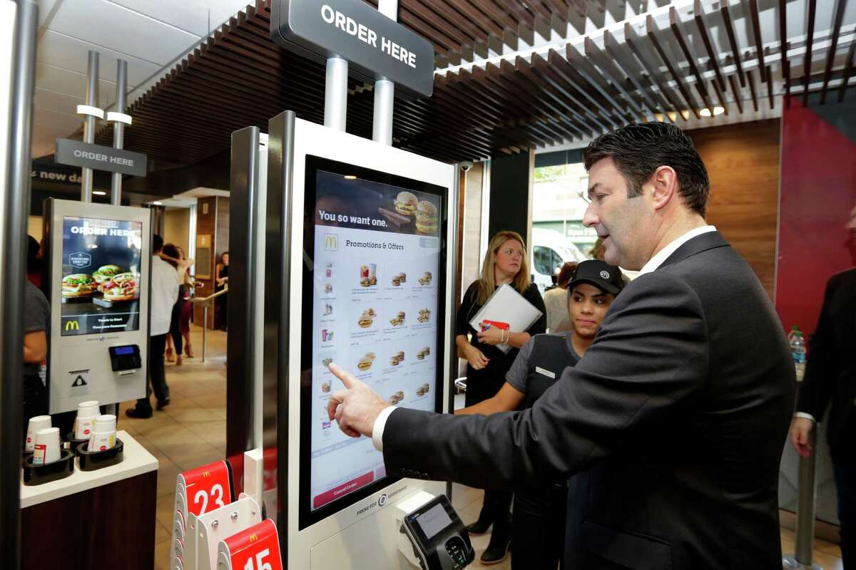 McDonald's CEO Steve Easterbrook demonstrates an order kiosk, with cashier Esmirna DeLeon, during a presentation at a McDonald's restaurant in New York's Tribeca neighborhood last month. Restaurant chains including McDonald's and Olive Garden are rolling out options like ordering kiosks.