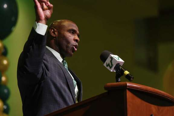 Charlie Strong flashes a familiar sign during a news conference announcing his arrival as the new coach of the South Florida Bulls.