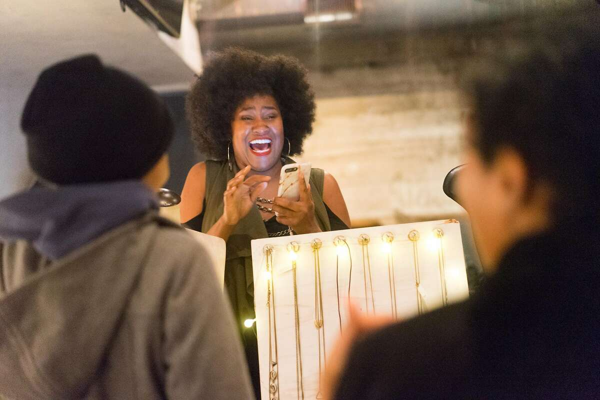 Candice Cox of CanDid Art speaks with customers during the Noire Holiday Pop Up at Era in Oakland, Calif. on Thursday, Dec. 15, 2016. Just Be., a collective of female creators showed their works to inspire black entrepreneurship.