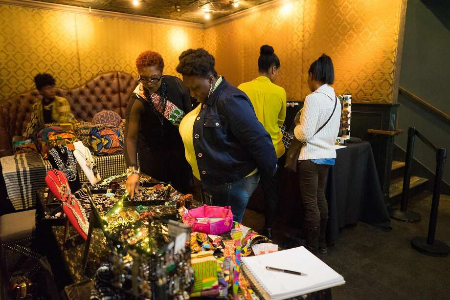 Yvonne Prevost, second from left, shows off her creative works to customers during the Noire Holiday Pop Up at Era in Oakland, Calif. on Thursday, Dec. 15, 2016. Just Be., a collective of female creators showed their works to inspire black entrepreneurship. Photo: James Tensuan, Special To The Chronicle