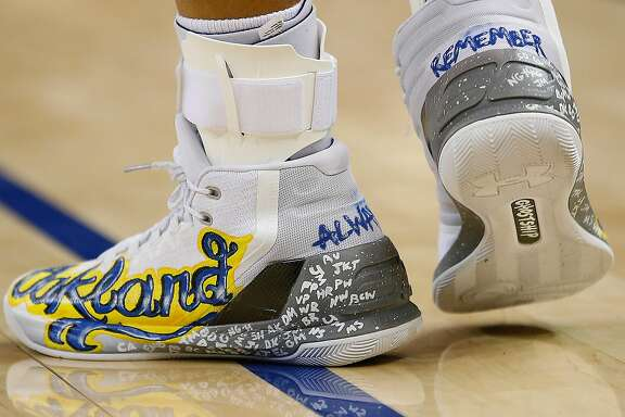 Golden State Warriors guard Stephen Curry (30) shows his tribute on his shoes for the Oakland ghostship fire victims during the second half against New York Knicks in a NBA game at Oracle Arena in Oakland, Calif., on Thursday, Dec. 15, 2016. Warriors won 103-90.