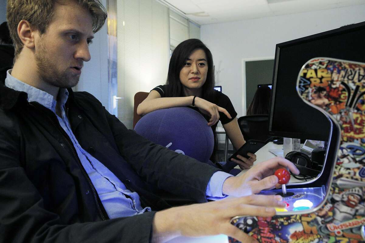 Ernestine Fu, right, watches Michael Piech play with a vintage video game emulator to get ideas for new games for Blackstorm at the Blackstorm headquarters in Mountain View, Calif., on Wednesday, December 14, 2016. Mountain View-based Blackstorm creates software that it licenses to companies so that the firms can embed their apps within other popular apps like Facebook, without having consumers download an additional separate app though a cumbersome process through the Apple App or Google Play stores.