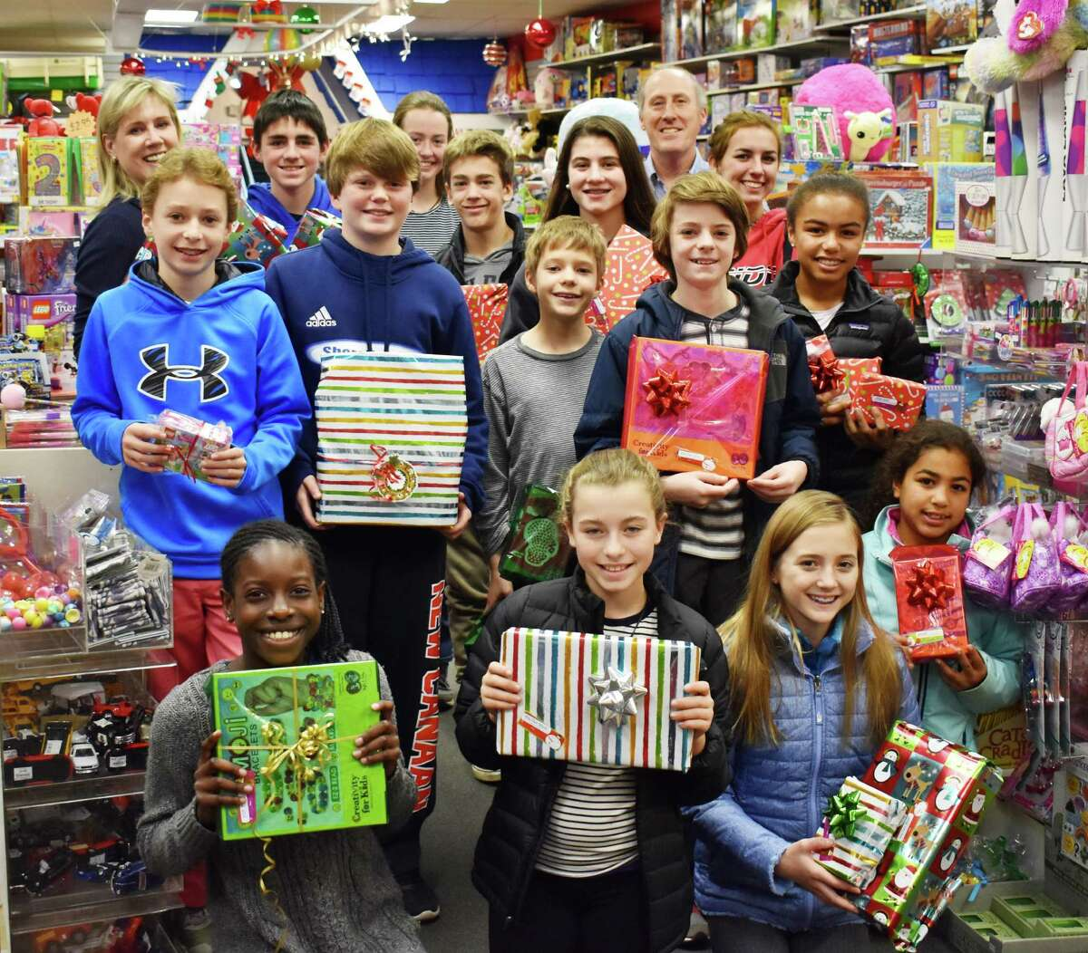 Kids from First Presbyterian Church of New Canaan show off the toys they purchased Dec. 4 at New Canaan Toy Store to donate to the nonprofit, Filling in the Blanks.