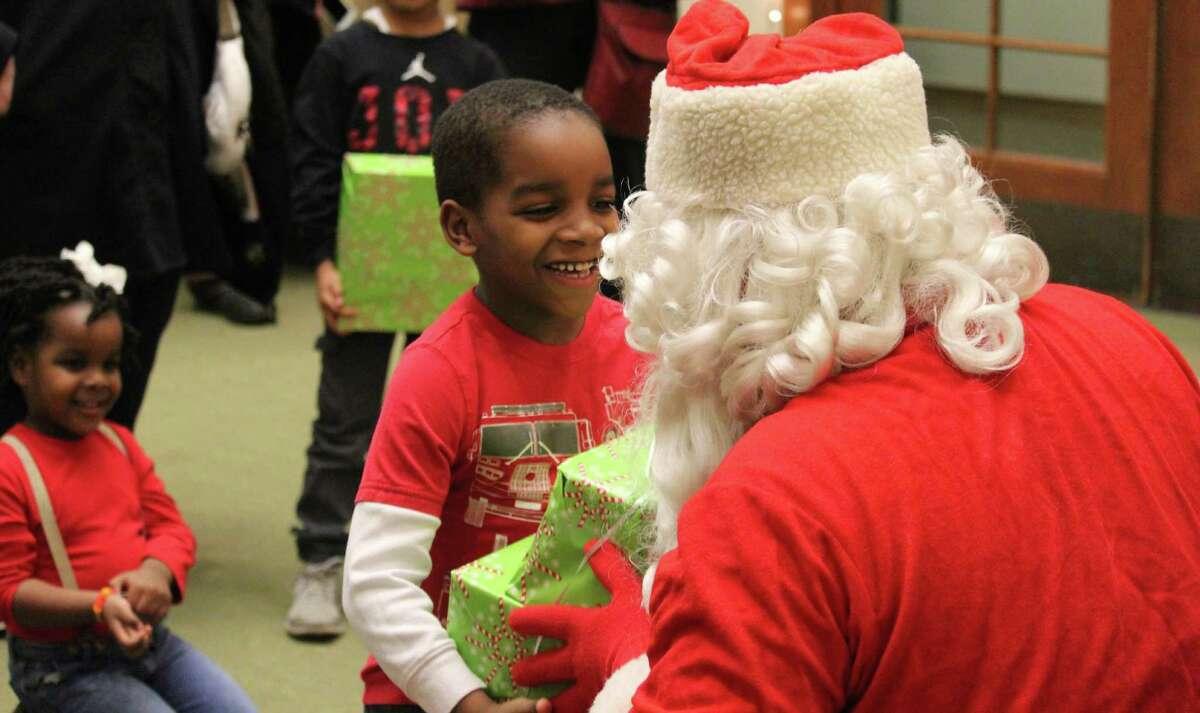 Malik Seme smiles as he receives his gift from Santa.