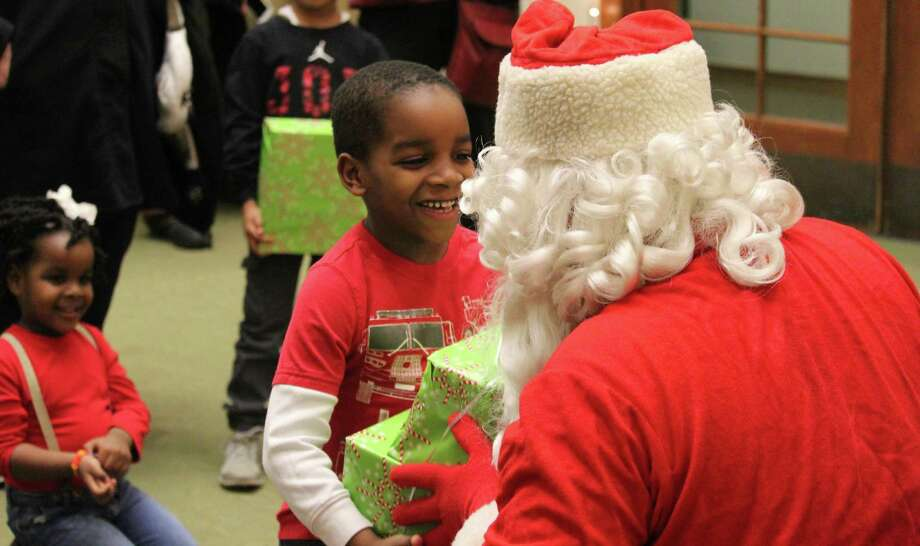 Malik Seme smiles as he receives his gift from Santa. Photo: Chris Marquette / Hearst Connecticut Media / Westport News