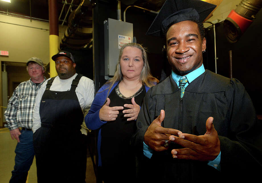 From left, Lamar Institute of Technology welding instructors Jason Bingham, Alex Lewis, interpreter Mary Alexander and graduate Joseph Guidry, showing the sign for welder, gather in the work bays. Guidry has earned his welding certification after completing his studies at Lamar Institute of Technology. Guidry lost his hearing when he was two and a half years old and has relied on the aid of services for the hearing impaired throughout his life. The 2014 West Brook graduate was provided an American Sign Language interpreter throughout his time at LIT and will now be pursuing work in the welding field. Photo taken Thursday, December 15, 2016 Kim Brent/The Enterprise Photo: Kim Brent / Beaumont Enterprise