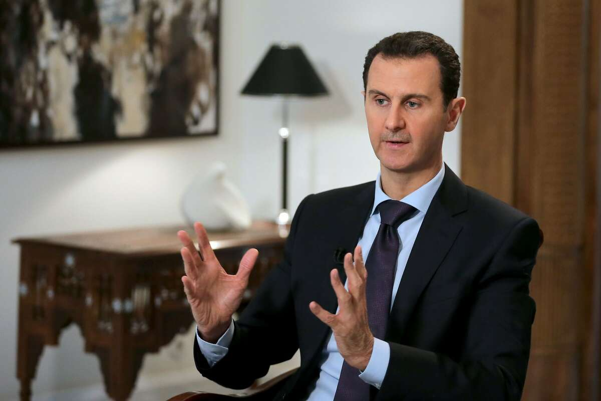 (FILES) This file photo taken on February 11, 2016 shows Syrian President Bashar al-Assad gesturing during an exclusive interview with AFP in the capital Damascus. Written off by the West, Assad has defied all expectations of his downfall, thanks to his iron will but also his crucial alliances with Russia and Iran. / AFP PHOTO / JOSEPH EIDJOSEPH EID/AFP/Getty Images