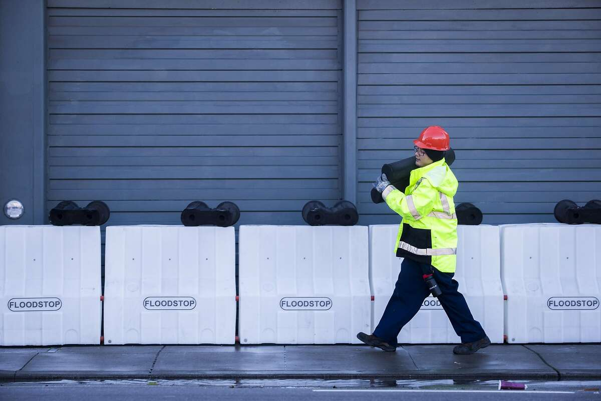 In this 2016 file photo, workers with SFPUC remove flood barriers near the intersection of 17th St. and Folsom Street. The San Francisco Public Utilities Commission is deploying flood barriers in advance of a major storm set to strike the Bay Area.