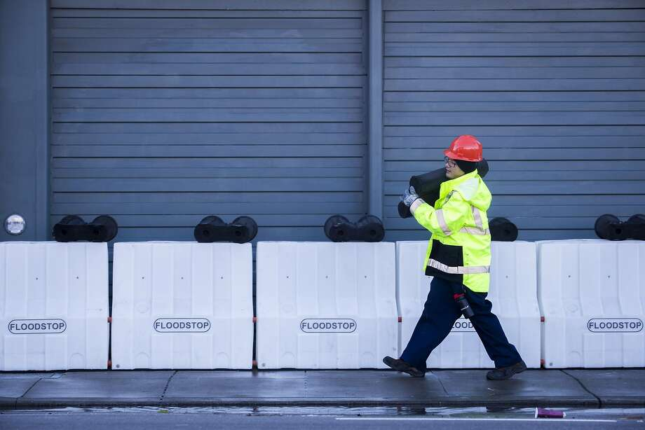 In this 2016 file photo, workers with SFPUC remove flood barriers near the intersection of 17th St. and Folsom Street. The San Francisco Public Utilities Commission is deploying flood barriers in advance of a major storm set to strike the Bay Area. Photo: Eric Kayne, Special To The Chronicle