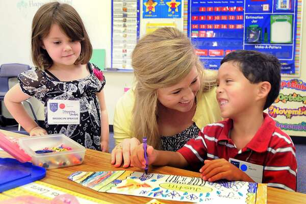 Powell Elementary School first year teacher Abigail Ott, A Caney Creek High High School and Texas A&M graduate, helps her kindergarten students Brooklyn Sprague and James Loera during the first day of school. School started today for Conroe ISD. Photo by David Hopper