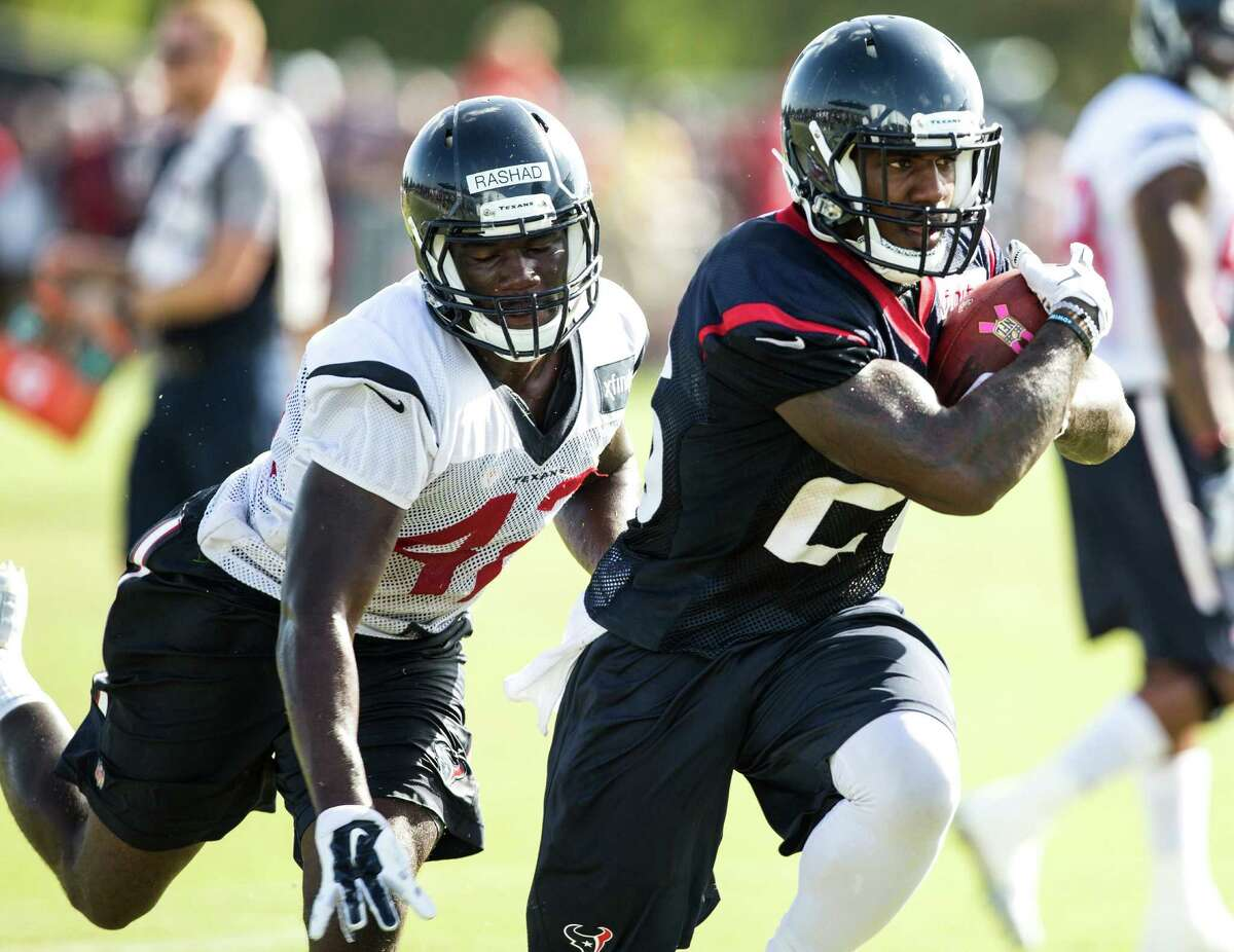 Houston Texans running back Lamar Miller (26) runs with the football past linebacker Shakeel Rashad (42) after making a catch during Texans training camp at Houston Methodist Training Center on Monday, Aug. 1, 2016, in Houston. ( Brett Coomer / Houston Chronicle )