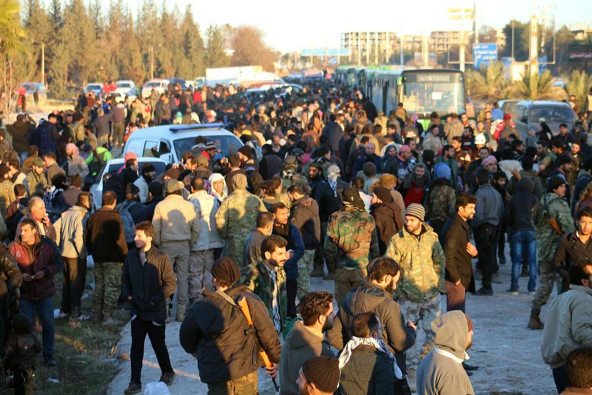 This image released on Thursday, Dec. 15, 2016 by Aleppo 24, shows residents gathered near green government buses for evacuation from eastern Aleppo, Syria. The evacuation of eastern Aleppo stalled Friday after an eruption of gunfire, as the Syrian government and rebels threw accusations at each other, raising fears that a peaceful surrender of the opposition enclave could fall apart with thousands of people believed to be still inside. (Aleppo 24 via AP)