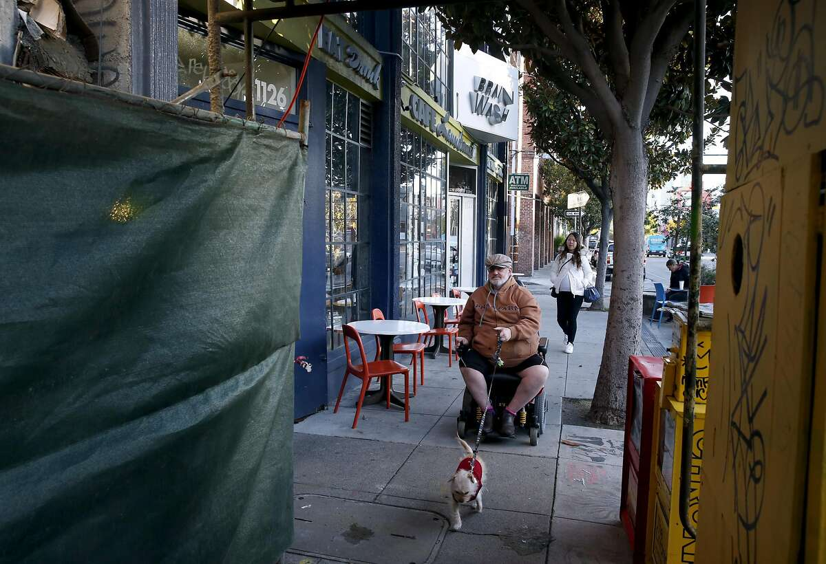 Pedestrians stroll past the Brainwash cafe and laundromat on Folsom Street towards scaffolding for a construction project next door in San Francisco, Calif. on Friday, Dec. 16, 2016. Owner Jeff Zalles has noticed a dramatic drop in business ever since a large residential development currently under construction broke ground next door to the Brainwash and is concerned he may have to shut down.